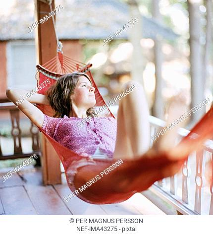 A Scandinavian woman laying in a hammock