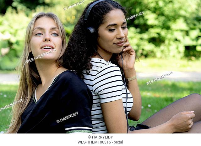 Two girlfriends in a park listening music