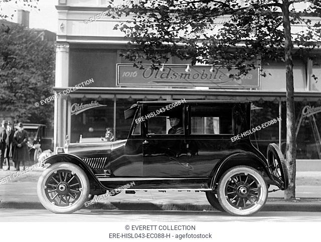 1922 Oldsmobile with a four cylinder engine sold for about $1650 ($23,600 in 2016). In the background is an Oldsmobile dealership in Washington, D.C