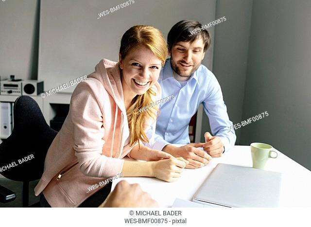Portrait of happy colleagues at desk in office