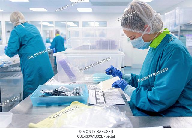 Worker making notes in clean room of surgical instruments factory