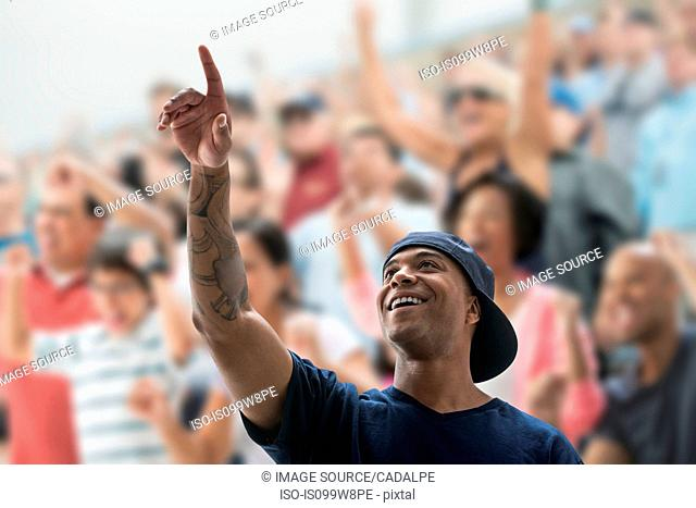 Man at sports game, pointing up