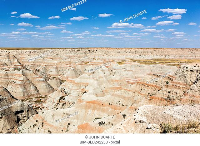 Layered rock formations under blue sky, Badlands National Park, South Dakota, United States
