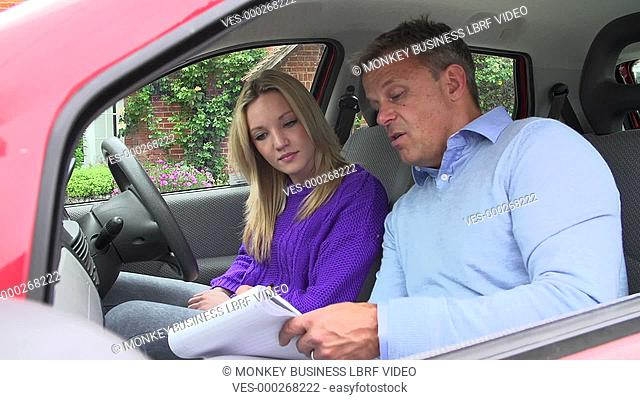 Teenage girl sits in car with driving instructor as he explains theory.Shot on Sony FS700 in PAL format at a frame rate of 25fps
