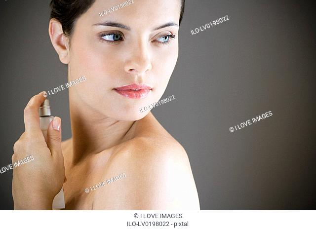 Young woman spraying perfume on her neck