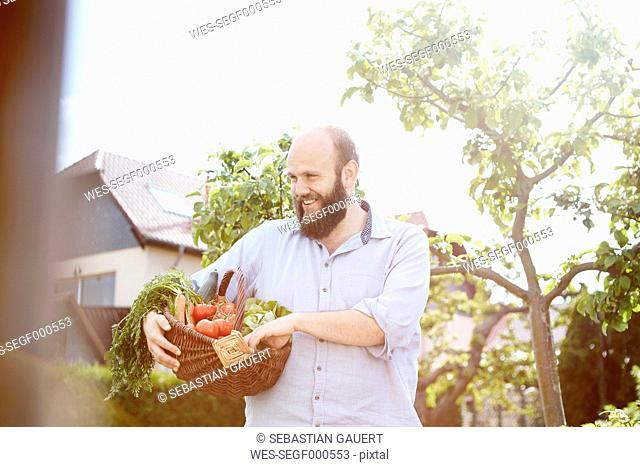 Young man standing in garden, basket with fresh vegetables