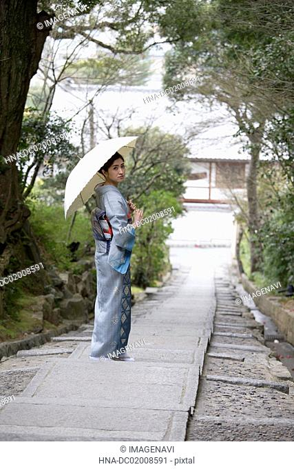 Young Japanese woman in kimono with parasol walking on stone stairs