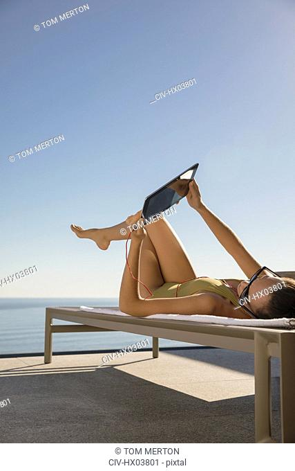 Woman sunbathing, using digital tablet on lounge chair on sunny patio