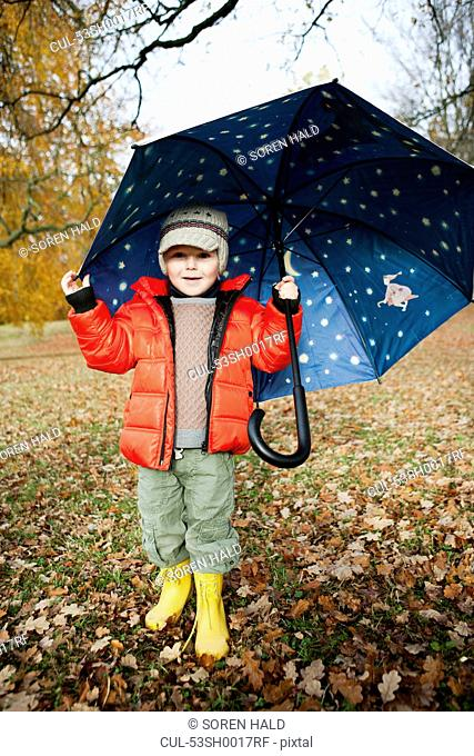 Boy in rain boots and umbrella in park