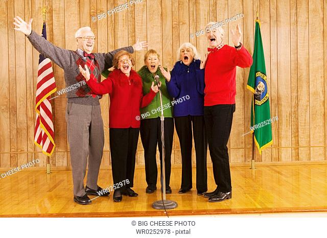 Enthusiastic elderly people singing on stage