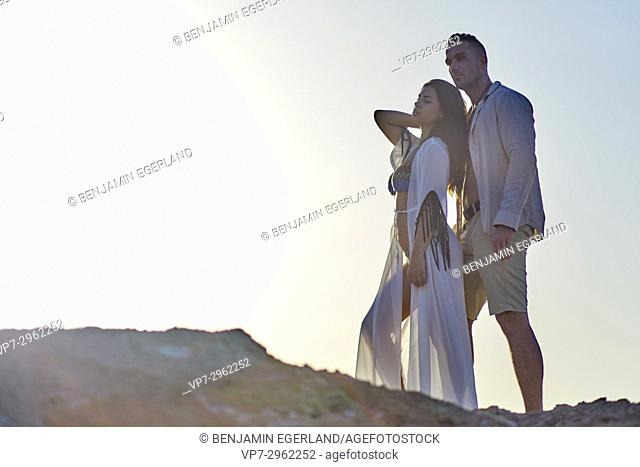 young couple in evening sun at beach. Greek ethnicity. In holiday destination Hersonissos, Crete, Greece