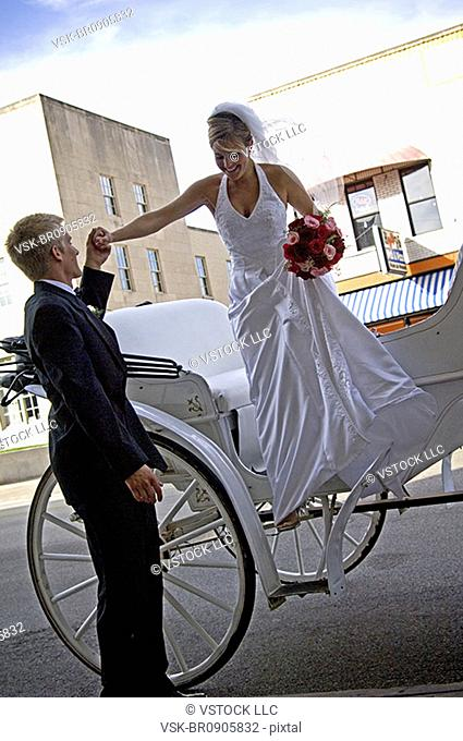Bride and groom getting out of carriage