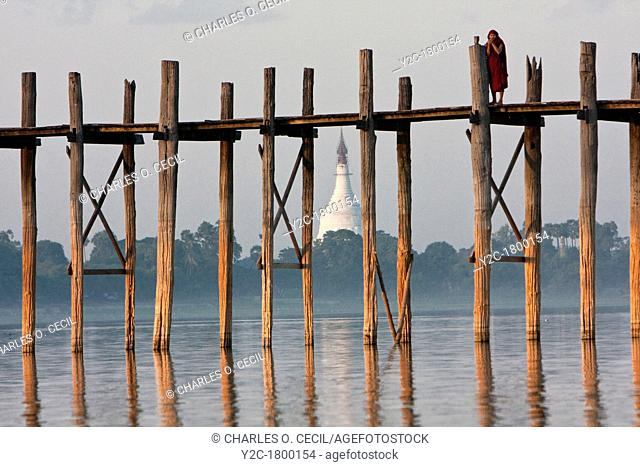 Myanmar, Burma, Mandalay, Amarapura  Buddhist Monk on the U Bein Bridge at the end of the day  The teak footbridge is 200 years old, and 1300 yards long