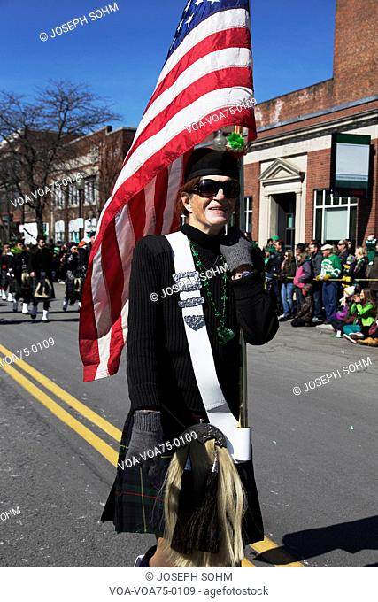 Woman marches with US Flag, St. Patrick's Day Parade, 2014, South Boston, Massachusetts, USA
