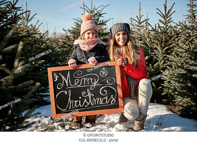 Girl and mother in christmas tree forest with merry christmas sign, portrait