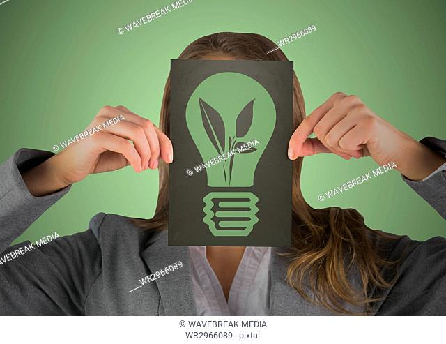 Business woman with black card over face showing green lightbulb graphic against green background