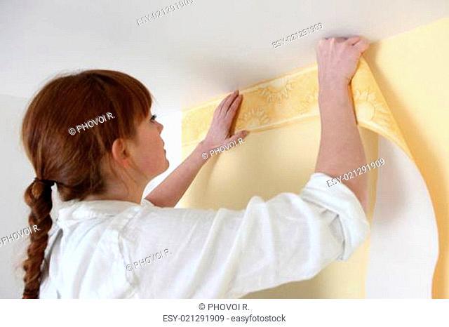 Woman putting up a wallpaper border