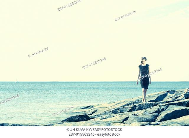 Fashionable woman walking on the rocky shore, the sailboat and horizon on background