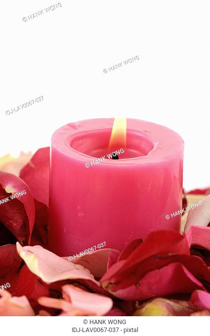 Candle lit up near rose petals