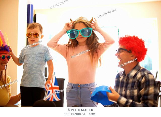 Family playing dress up, wearing funny hats and glasses, laughing