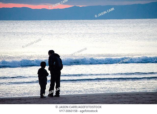 Son and Father are looking at something around their feet in a winter beach scene. Kanagawa, Japan