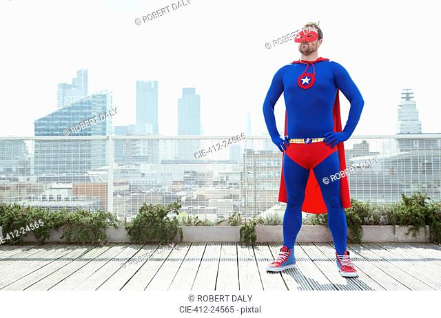 Superhero standing with hands on hips on city rooftop