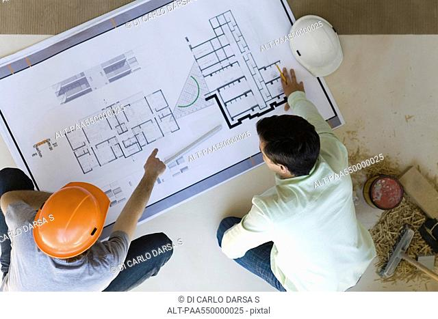 Two men reviewing blueprint spread out on floor