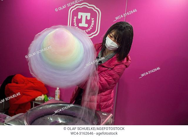 31. 12. 2017, Tokyo, Japan, Asia - A young woman sells multicoloured candy floss at a shop on Takeshita street in Harajuku