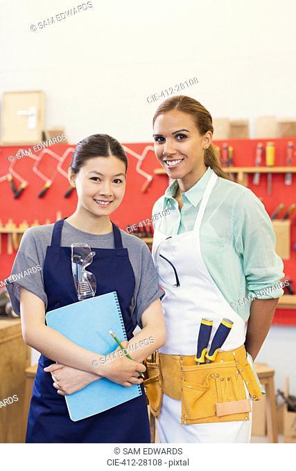 Portrait confident female carpenters in workshop