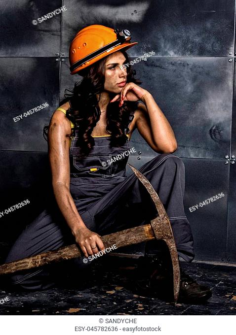 sexy female miner worker with pickaxe, in coveralls over his naked body, sitting on the floor on backdrop of steel wall