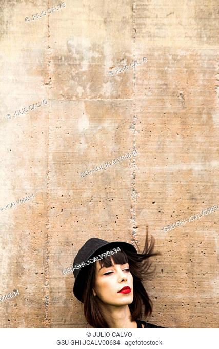 Head and Shoulders Portrait of Woman with Red lipstick and Hat against Cement Wall