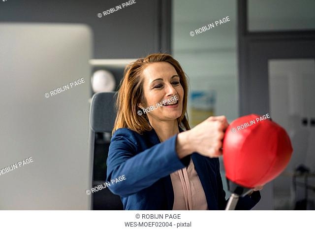 Businesswoman boxing a punchingball in her office