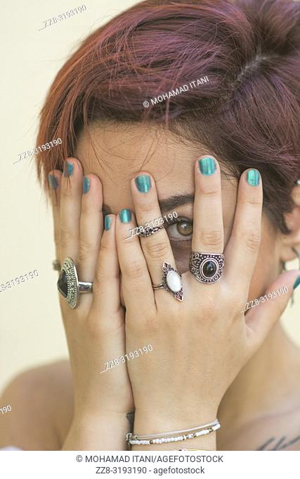 Scared woman hiding face with hands looking through fingers