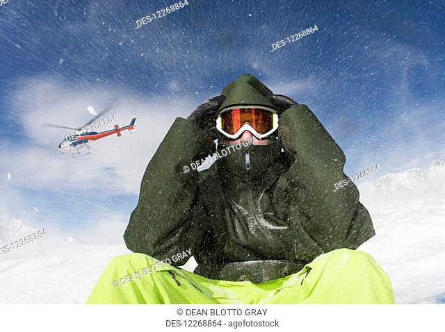 A young man sits in winter apparel and a ski mask while a helicopter flies overhead and blows snow; Methven, New Zealand