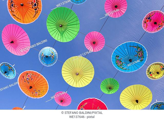 Scores of colourful umbrellas suspended in the air at the umbrella festival in Bo Sang near Chiang Mai, Thailand