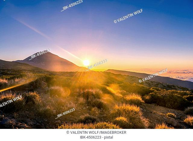 Sunset, sunset glow, cloudy sky, Volcano Teide and volcano landscape, backlit scenery, national park El Teide, Tenerife, Canary Islands, Spain