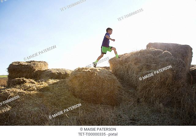 Boy (6-7) running on straw bales at sunset