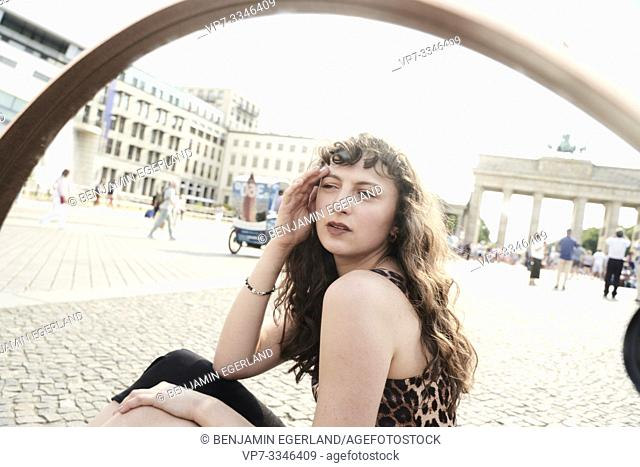 young woman sitting next to touristic landmark Brandenburger Tor, Brandenburg Gate, in Berlin, Germany