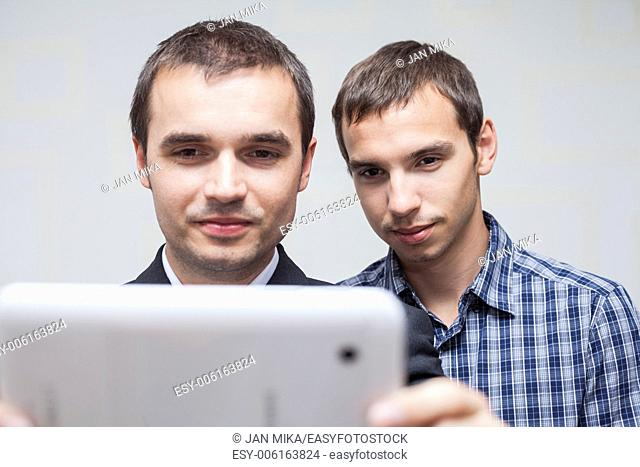 Closeup of two smiling businessmen looking at digital tablet