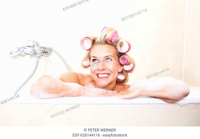 blond woman sitting in bathtub with curlers in her hair