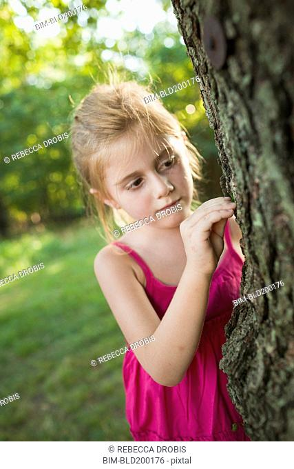 Caucasian girl looking at tree
