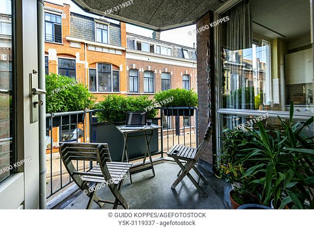 Tilburg, Netherlands. Decorated balcony living space inside a down town apartment, with view towards opposite neigbouring residential buildings and houses