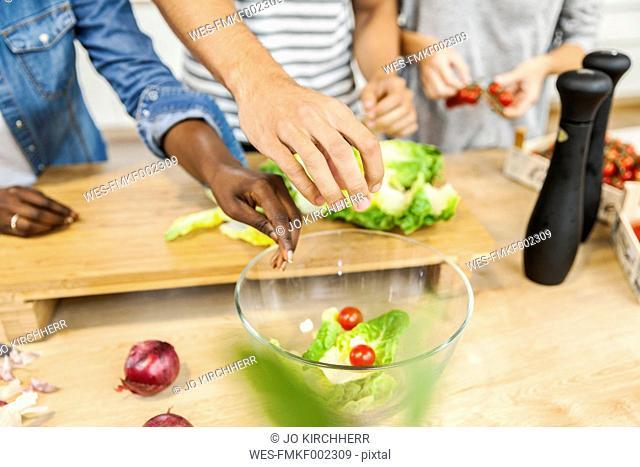 Hands over salad bowl in kitchen