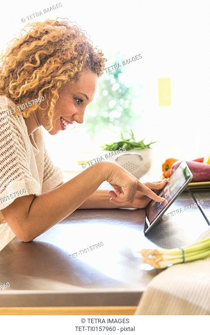 Young woman using digital tablet in kitchen