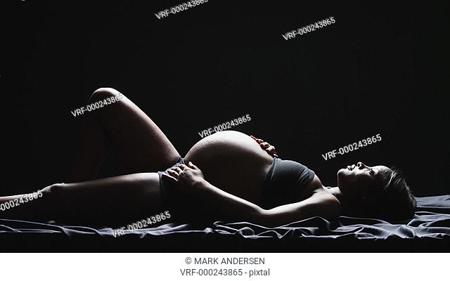 WS ZI MS Studio shot of pregnant woman lying against black background