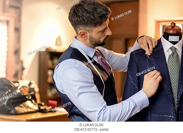 Tailor adjusting suit on dressmakers model in menswear shop
