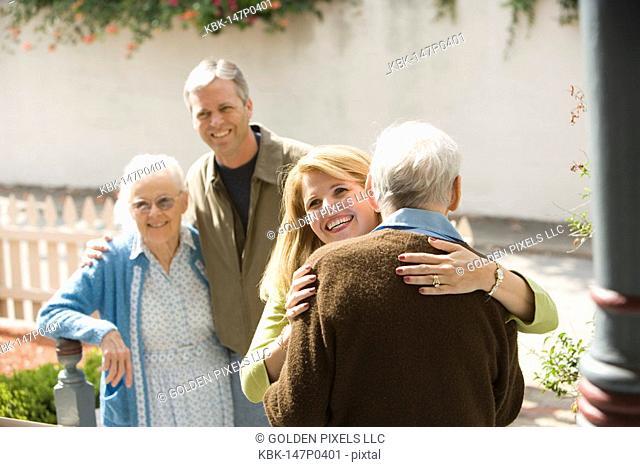 Woman hugging senior man while man and senior woman watch