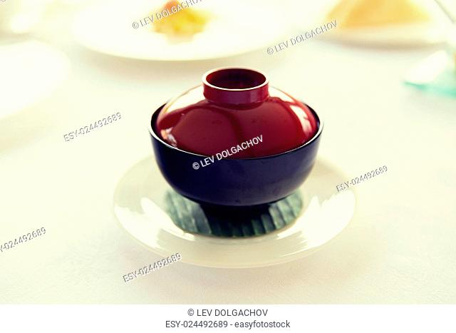 cooking, eating, food and kitchen concept - ceramic pot with hot dish on restaurant table