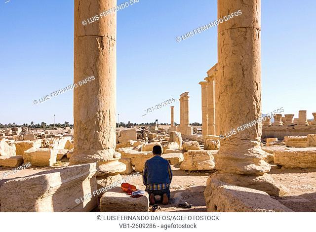 Muslim man praying at the ruins at Palmyra, Syria