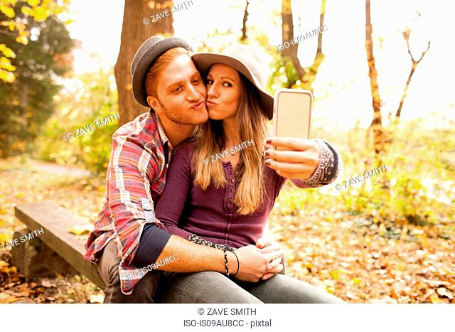 Young couple on bench taking smartphone selfie in autumn forest